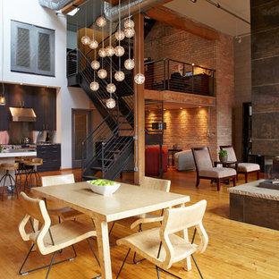 Idee per una sala da pranzo aperta verso il soggiorno industriale con pareti bianche, pavimento in legno massello medio, camino bifacciale e cornice del camino piastrellata