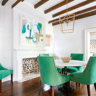 Modelo de comedor minimalista, pequeño, cerrado, con paredes blancas, suelo de madera en tonos medios, chimenea tradicional, marco de chimenea de madera y suelo marrón