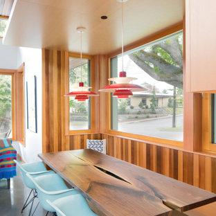 Ispirazione per una sala da pranzo minimalista con pareti marroni, pavimento in cemento e pavimento grigio