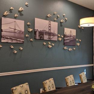 Immagine di una grande sala da pranzo aperta verso il soggiorno chic con pareti blu, pavimento in laminato e pavimento marrone