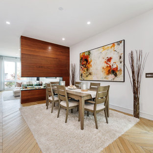 Example of a trendy light wood floor and beige floor dining room design in Chicago with white walls, a two-sided fireplace and a wood fireplace surround