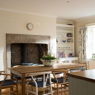 Immagine di una sala da pranzo country con pareti bianche, parquet chiaro, stufa a legna e cornice del camino in cemento