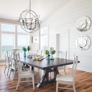 Foto di una grande sala da pranzo aperta verso il soggiorno costiera con pareti bianche, pavimento in legno massello medio e pavimento marrone
