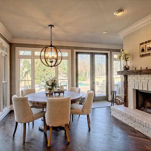 Idee per una sala da pranzo country con pareti grigie, pavimento in legno massello medio, camino bifacciale e cornice del camino in mattoni