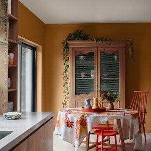 Foto di una sala da pranzo aperta verso la cucina chic con pareti arancioni, parquet chiaro e pavimento beige