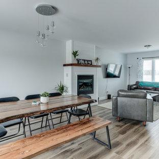 На фото: столовая в стиле модернизм с синими стенами, полом из винила, стандартным камином, фасадом камина из вагонки и коричневым полом с