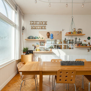 This is an example of a medium sized eclectic kitchen/dining room in Other with white walls, light hardwood flooring and beige floors.