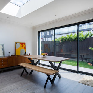 Contemporary open plan dining room in London with light hardwood flooring, grey floors and white walls.