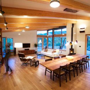 Idee per una sala da pranzo aperta verso il soggiorno design con pareti beige, pavimento in legno massello medio, stufa a legna e cornice del camino in metallo
