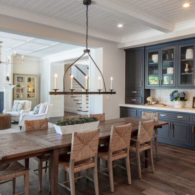 Mid-sized beach style dark wood floor, beige floor and exposed beam breakfast nook photo in San Francisco with beige walls, a standard fireplace and a stone fireplace