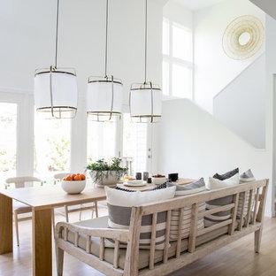 Idee per una sala da pranzo aperta verso il soggiorno stile marinaro di medie dimensioni con pareti bianche, parquet chiaro, camino bifacciale e cornice del camino in mattoni