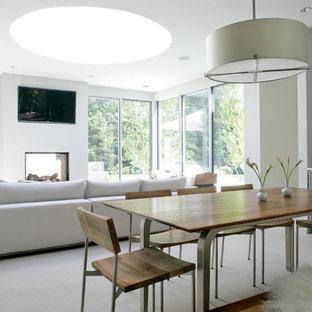 Ejemplo de comedor moderno, de tamaño medio, abierto, con paredes blancas, suelo de mármol, chimenea tradicional, marco de chimenea de hormigón y suelo gris