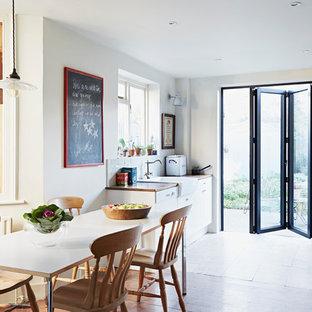 Ispirazione per una sala da pranzo aperta verso la cucina boho chic di medie dimensioni con pareti bianche
