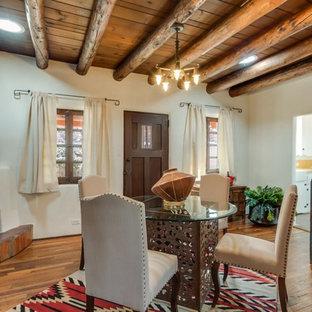 アルバカーキの中サイズのサンタフェスタイルのおしゃれなダイニング (ベージュの壁、無垢フローリング、コーナー設置型暖炉、漆喰の暖炉まわり、茶色い床) の写真