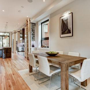 Стильный дизайн: кухня-столовая среднего размера в современном стиле с серыми стенами, светлым паркетным полом, двусторонним камином и фасадом камина из штукатурки - последний тренд
