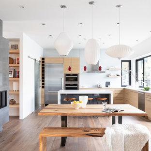 Modelo de comedor de cocina actual, grande, con suelo de madera en tonos medios, paredes blancas, chimenea lineal, marco de chimenea de hormigón y suelo marrón