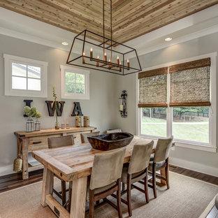 Ejemplo de comedor campestre, cerrado, con paredes grises, suelo de madera en tonos medios, chimenea de esquina y suelo marrón