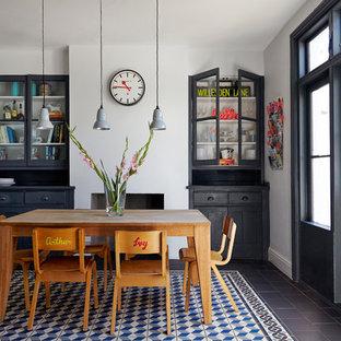 Esempio di una sala da pranzo aperta verso la cucina boho chic di medie dimensioni con pareti grigie, pavimento in gres porcellanato e camino classico