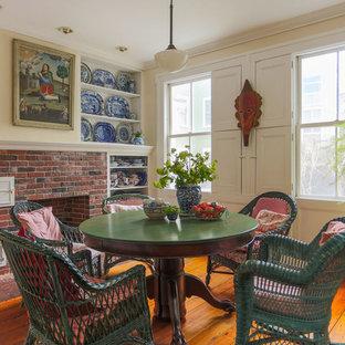 Ispirazione per una sala da pranzo eclettica con pareti beige, pavimento in legno massello medio, camino classico e cornice del camino in mattoni