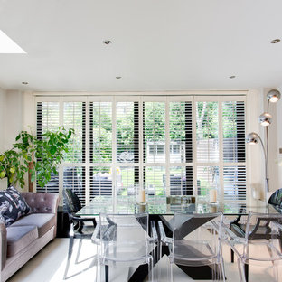 Mid-sized eclectic dining room photo in London with white walls and no fireplace