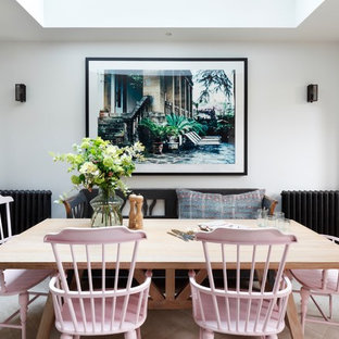 Medium sized bohemian open plan dining room in London with white walls and light hardwood flooring.