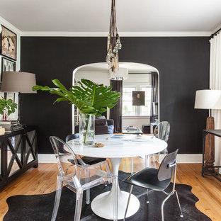 Ispirazione per una sala da pranzo boho chic con pareti nere, pavimento in legno massello medio e pavimento marrone