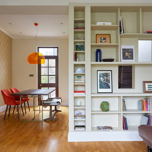 Photo of a medium sized eclectic dining room in Surrey with medium hardwood flooring, multi-coloured walls and orange floors.