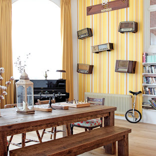 Example of a large eclectic dining room design in London with yellow walls