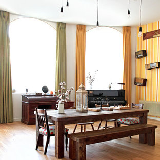 Diseño de comedor ecléctico, grande, abierto, con paredes amarillas y suelo de madera en tonos medios