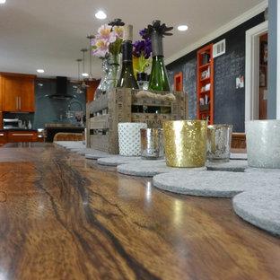 Ejemplo de comedor de cocina ecléctico, grande, con paredes negras, suelo de corcho, chimenea tradicional y marco de chimenea de madera