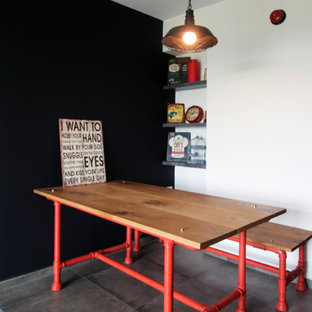 Inspiration for an industrial dining room remodel in Singapore with black walls