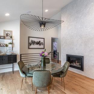 Foto di una sala da pranzo aperta verso il soggiorno minimal con pareti bianche, pavimento in legno massello medio, camino lineare Ribbon, cornice del camino in cemento e pavimento marrone