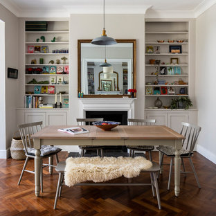 Inspiration for a small contemporary kitchen/dining room in London with grey walls, dark hardwood flooring, a standard fireplace, a metal fireplace surround and brown floors.