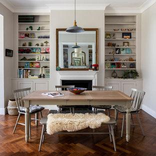 Идея дизайна: маленькая кухня-столовая в современном стиле с серыми стенами, темным паркетным полом, стандартным камином, фасадом камина из металла и коричневым полом