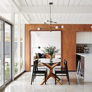 Cette image montre une salle à manger ouverte sur la cuisine vintage avec un mur blanc, béton au sol, un sol gris, un plafond en lambris de bois et un plafond voûté.