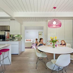 Foto di una sala da pranzo moderna con pareti gialle e pavimento in legno massello medio