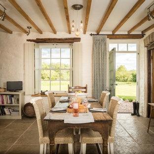 Immagine di una sala da pranzo aperta verso la cucina rustica di medie dimensioni con pavimento in pietra calcarea, pavimento beige e pareti bianche