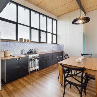 Immagine di una sala da pranzo aperta verso il soggiorno design di medie dimensioni con pareti bianche, pavimento in laminato e stufa a legna