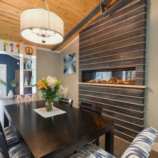 Esempio di una sala da pranzo aperta verso la cucina boho chic di medie dimensioni con pareti verdi, pavimento in bambù, camino sospeso, cornice del camino in legno e pavimento marrone