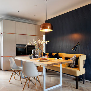 This is an example of a contemporary kitchen/dining room in London with black walls and light hardwood flooring.