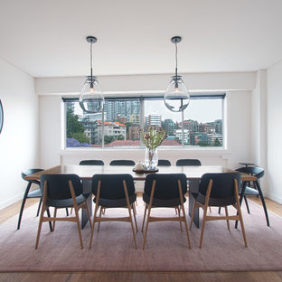 Photo of a scandinavian dining room in Sydney with white walls, medium hardwood floors and brown floor.