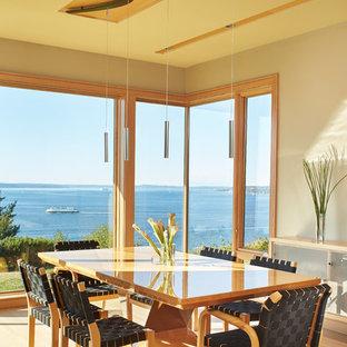 Immagine di una sala da pranzo aperta verso la cucina design di medie dimensioni con pareti beige e pavimento in legno massello medio