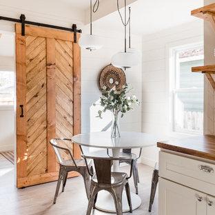 Idées déco pour une petit salle à manger ouverte sur la cuisine campagne avec un mur blanc, sol en stratifié et un sol gris.