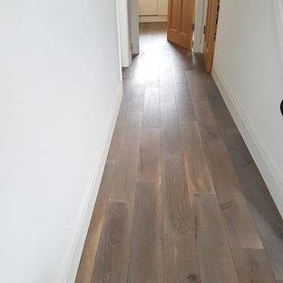 Esempio di una grande sala da pranzo aperta verso il soggiorno rustica con pareti beige, pavimento in legno massello medio, stufa a legna, cornice del camino piastrellata e pavimento multicolore