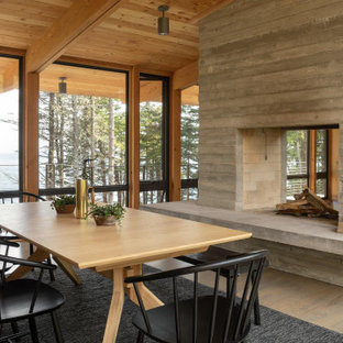 This is an example of a mid-sized country open plan dining in Portland Maine with brown walls, medium hardwood floors, a two-sided fireplace, a concrete fireplace surround and grey floor.