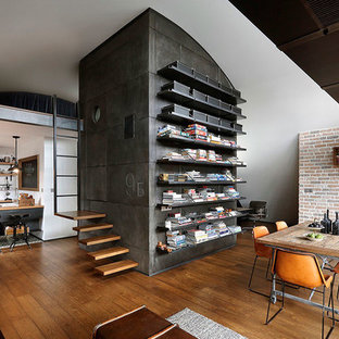 Enclosed dining room - mid-sized industrial medium tone wood floor enclosed dining room idea in Valencia with multicolored walls and a standard fireplace
