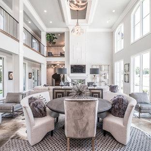 На фото: огромные гостиные-столовые в стиле современная классика с серыми стенами, паркетным полом среднего тона, двусторонним камином, фасадом камина из плитки и коричневым полом
