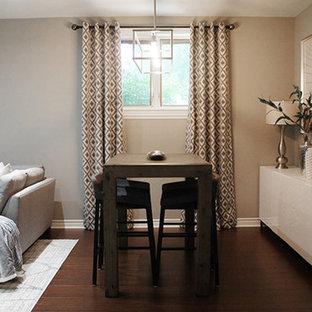 Imagen de comedor clásico renovado, de tamaño medio, abierto, con paredes grises, suelo de madera en tonos medios, chimenea tradicional y marco de chimenea de hormigón
