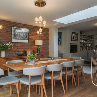 Photo of a medium sized contemporary open plan dining room in London with brown floors, white walls and dark hardwood flooring.