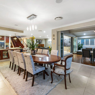 This is an example of a transitional kitchen/dining combo in Brisbane with beige walls and beige floor.